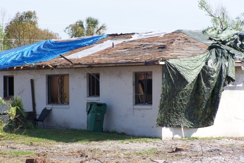 a hurricane-damaged house with a torn up roof